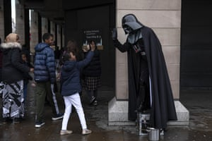 A young child hi-five's a performer dressed as Darth Vader outside the Houses of Parliament in London