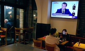 People dine at a restaurant in Saint-Jean-de-Luz, south-west France, as Emmanuel Macron gives an address on television