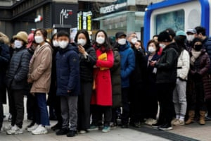 People wearing masks wait in a line to buy masks in front of a department store in Seoul, South Korea.
