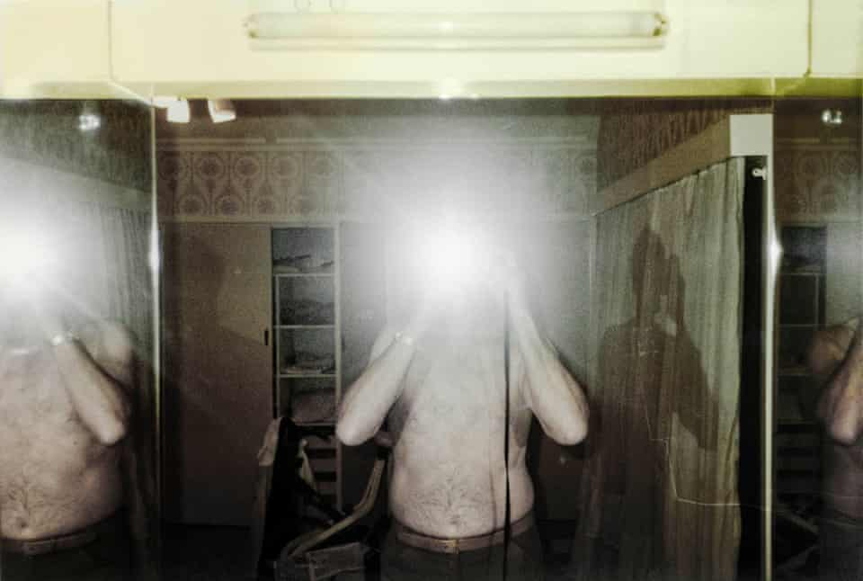 Sam Goldbloom taking a photo of himself in a mirror, with the flash obscuring his face