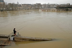 A man fishes on the flooded banks of the Seine