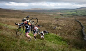 Cyclists carry their bicycles up a steep hill during the Three Peaks Cyclo-Cross in North Yorkshire