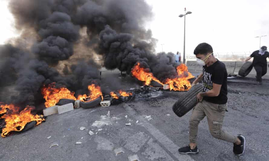A protester places burning tyres on a road in Khalde, Lebanon