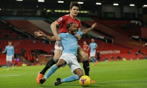 Manchester City's Raheem Sterling goes down under pressure from Harry Maguire.