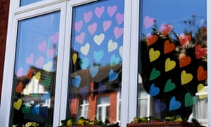 A rainbow image made of paper hearts in a window of a house in London