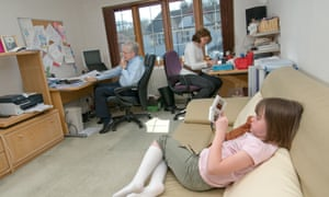 A man and woman at their home desks while a child sits nearby on a sofa.