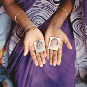 A woman holds photographs of the twins she recently delivered for a foreign couple at Hiranandani Hospital in Mumbai