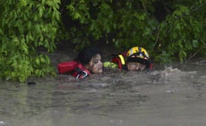 A firefighter rescues a woman from flood waters in San Marcos.