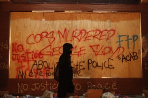 A person walks past a building covered with graffiti about the death of George Floyd