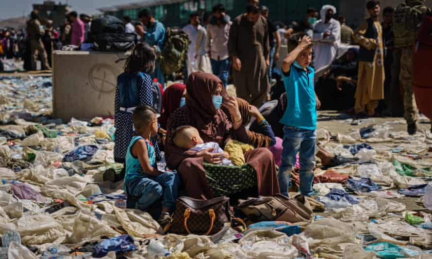 A woman is surrounded by her children as she sits amid a pile of debris in the processing area towards Abbey gate on Wednesday