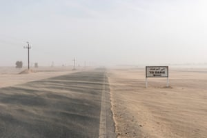 A sandstorm sweeps over a desert road.