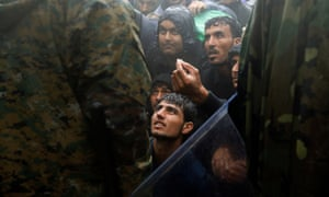 Migrants and refugees beg Macedonian police to allow passage to cross the border from Greece into Macedonia, 2015.