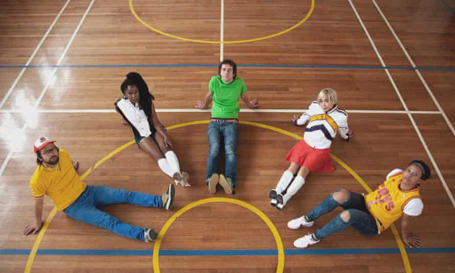 the go team members seen from above and sitting in a semicircle on a baskteball court