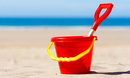 Red Bucket and Spade on Beach Holiday Vacation Concept<br>A4FM5B Red Bucket and Spade on Beach Holiday Vacation Concept