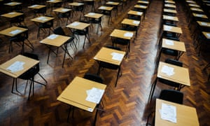 Rows of empty desks ready for GCSE school pupils to sit their exams in a school hall