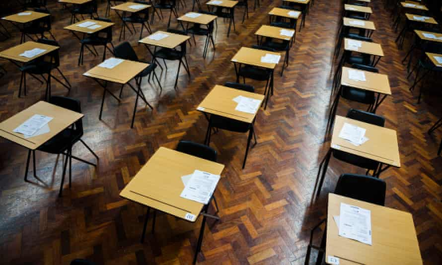 Rows of empty desks ready for pupils to sit their exams in a school hall.