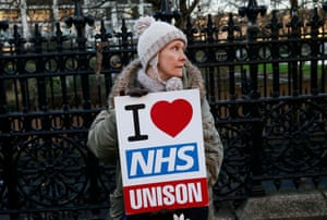 A woman holds an 'I love NHS' placard outside St Thomas' hospital in London