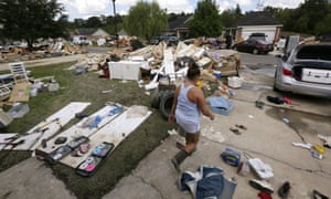 "A resident walks through a flood-damaged neighborhood in Louisiana. The state's governor has requested an addition $2 bn in emergency aid from the federal government. ""Simply put, we cannot recover without it,"" Edwards said at a House subcommittee hearing."