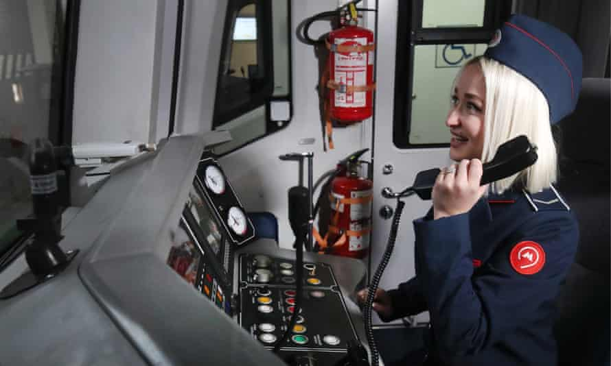 A female train driver uses the phone inside the cab of a train in the maintenance depot on Line 4 (Filyovskaya Line) of the Moscow Underground (Metro).