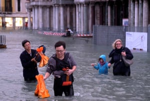 People walk in a flooded Saint Mark Square during a period of seasonal high water in Venice, Italy