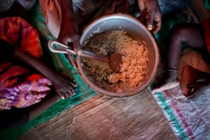 Sahera Abdi holds a pan containing the only rice she has to feed her five children