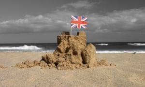 a damaged sandcastle on a beach with a union flag as a dark storm rolls in