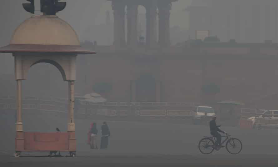 A man cycles past a government building amid heavy smog in Delhi