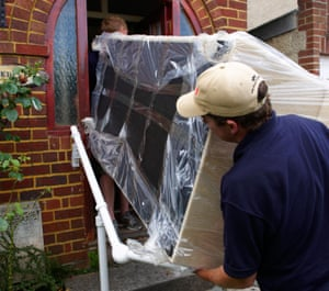 Two men pushing a plastic-wrapped sofa through the door of a brick building