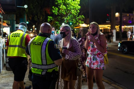 Police Officer Randy Perez (c) inform people about wearing protective face masks in the downtown area of Duval Street in Key West, Florida on September 18, 2020.