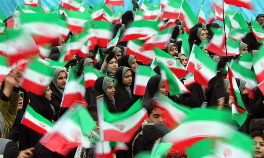 Female students wave Iranian national flags during a ceremony marking the anniversary of the 1979 Islamic Revolution, at the Azadi (Freedom) square in Tehran.
