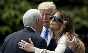 Melania Trump and Mike Pence embrace as they walk across the South Lawn of the White House on Friday.