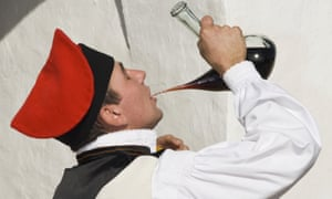 A man in traditional costume drinking wine out of a typical porrón.