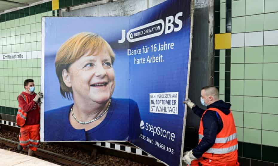 Workers remove an advertisement showing German chancellor Angela Merkel with a slogan that reads 'Mother of Nation – Thanks For 16 Years of Hard Work' before this weekend's elections in Hamburg.