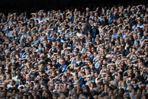 Manchester City fans shield their eyes from the afternoon sun.