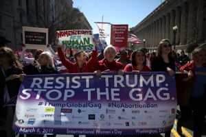 Protesters hold signs as they march to the White House during a march and rally to support women's health programmes and protest the White House global gag rule on March 8, 2017 in Washington DC.
