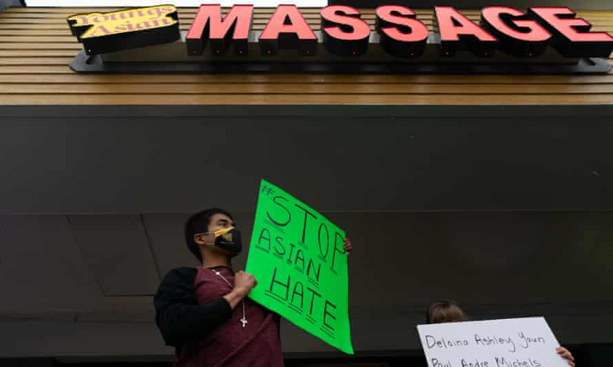 Jesus Estrella holds a sign of solidarity outside Youngs Asian Massage where four people were shot and killed on 17 March in Acworth, Georgia.