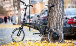 Hummingbird folding bike electric leaning against a tree among falling leaves