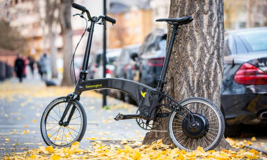 Hummingbird folding bike electric leaning against a tree among falling leaves
