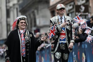 Pearly Kings and Queens wave Union flags as they walk during the New Year's Day parade in London