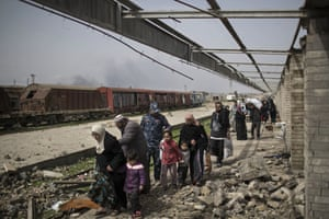 Iraqi civilians flee through a destroyed train station during fighting between Iraqi security forces and Islamic State militants