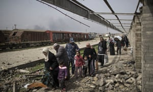 Iraqi civilians flee through a destroyed train station during fighting between Iraqi security forces and Islamic State militants on the western side of Mosul, on 19 March 2017.