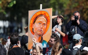 A protester holds a painting depicting Thunberg, titled Our House Is on Fire (Our Children Will Burn) by Julia Vanderbyl, during a rally in Paris.