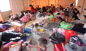 Central American mothers and their children take a place on the floor of a portable tent at the Humanitarian Respite Center Sacred Heart Catholic church in McAllen, Texas, earlier this month.