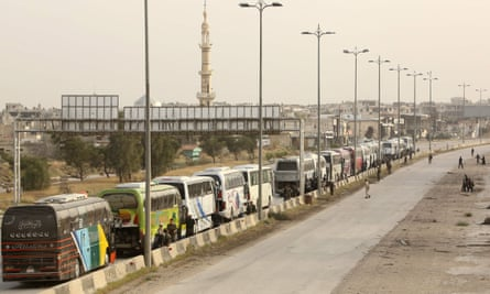 Syrian rebel fighters from the Ahrar al-Sham faction wait by buses