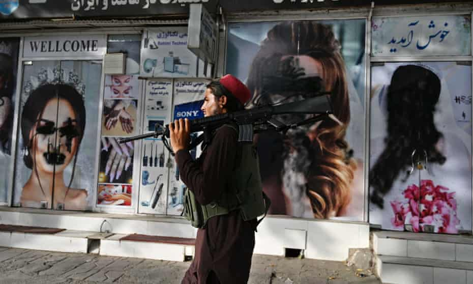 A Taliban fighter walks past vandalized images of women in front of a beauty salon in Kabul, Afghanistan.