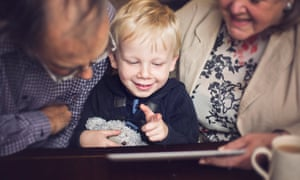 Young boy and grandparents look at a tablet. Picture posed by models.