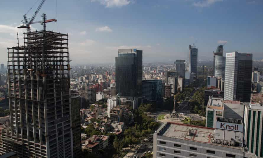 A crane sits on top of a partially constructed building on Reforma Avenue in Mexico City