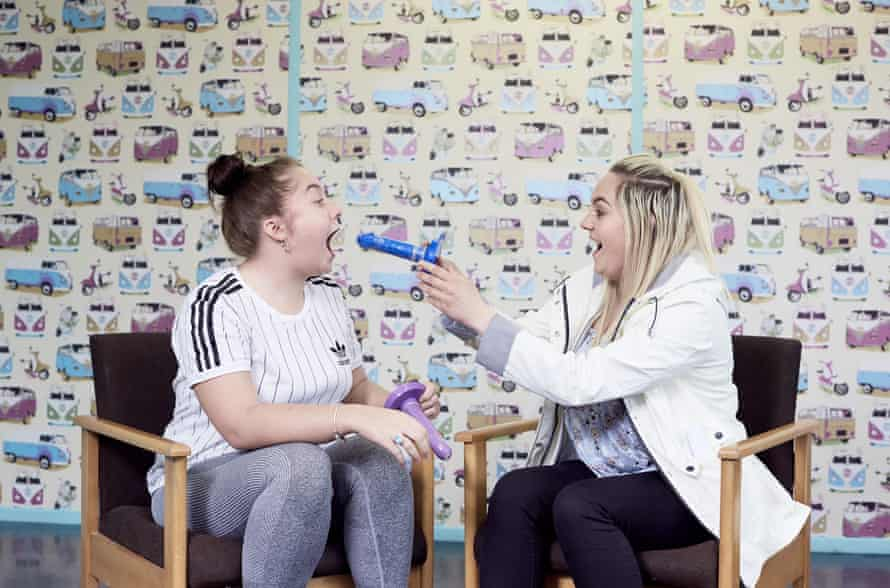 New mothers, aged 18, share a joke after learning how to put on condoms