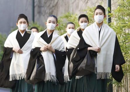 Takarazuka Music School students wear masks as they head to their graduation ceremony in Takarazuka, western Japan, on 2 March, amid the spread of the coronavirus.