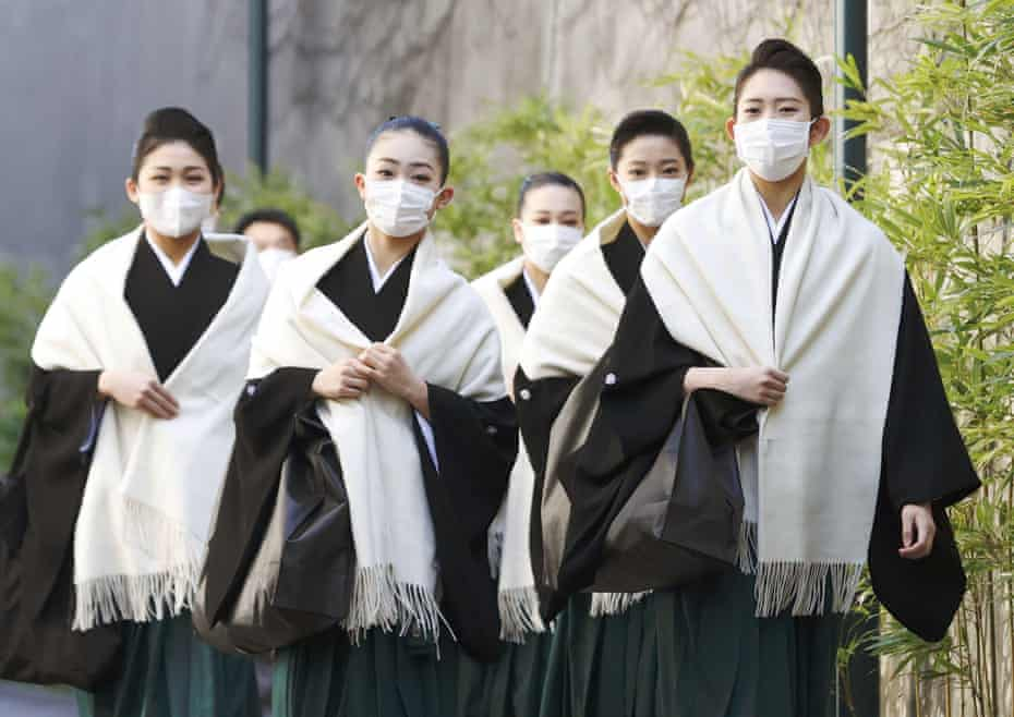 Takarazuka Music School students wear masks as they head to their graduation ceremony in Takarazuka, western Japan, on 2 March, amid the spread of the coronavirus.